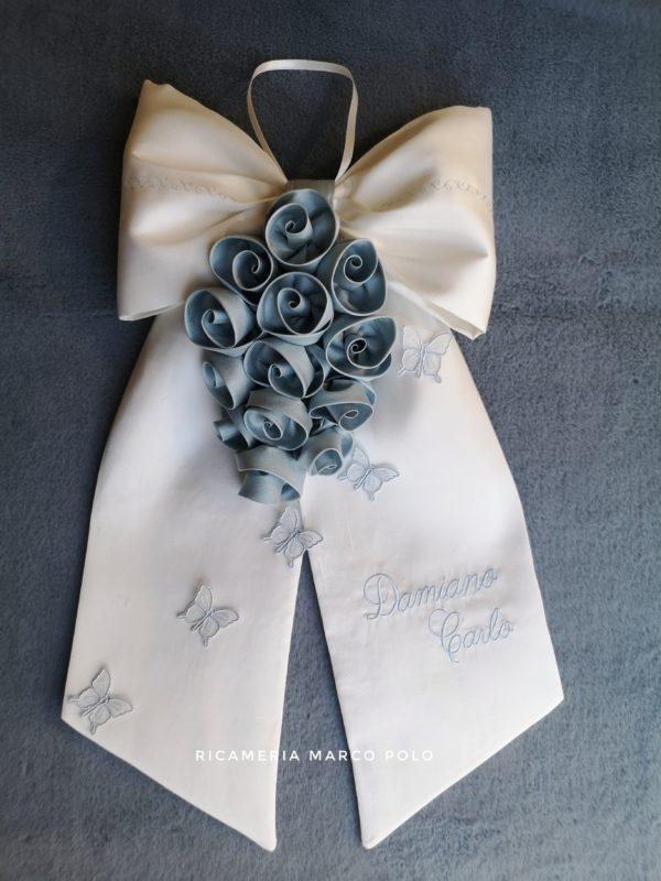 Cascata di rose azzurro polvere su fiocco in pura seta bianco