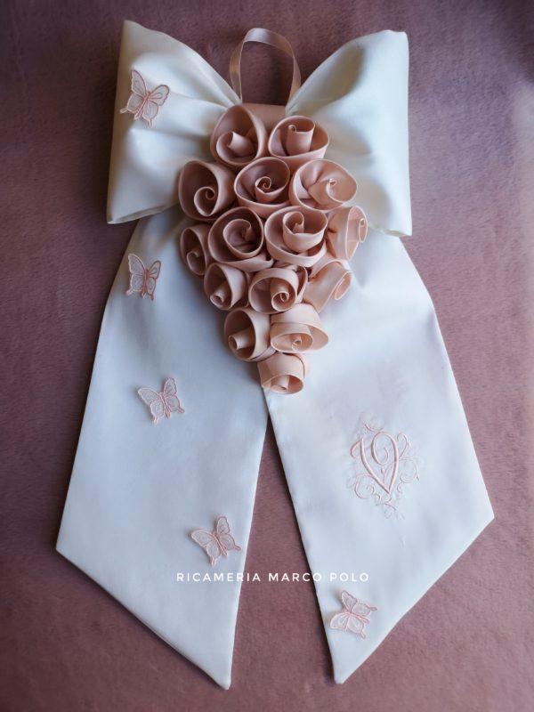 Cascata di rose cipria su fiocco in pura seta bianca