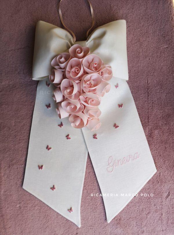 Cascata di rose cipria su fiocco lino panna