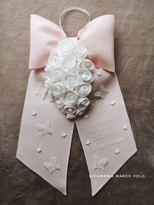 Cascata di rose bianche su lino rosa cipria