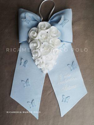 Cascata di rose bianche e farfalle su lino azzurro